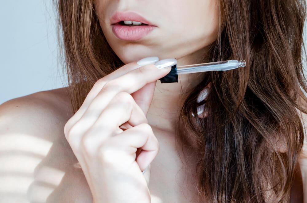 Woman applying hair serum